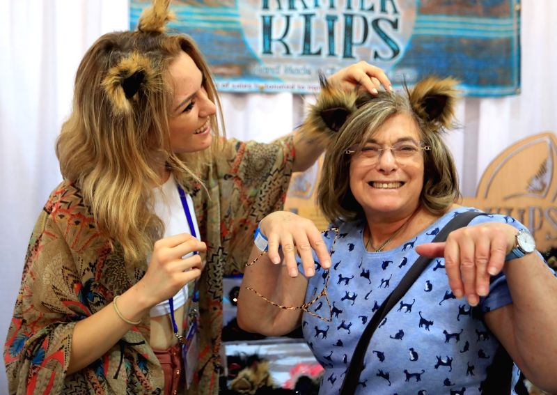 LOS ANGELES, Aug. 5, 2018 - An exhibitor helps a visitor wear a cat-ear headwear at the CatCon 2018 in Pasadena, Los Angeles County, the United States, Aug. 4, 2018. The two-day cat-centric pop ...