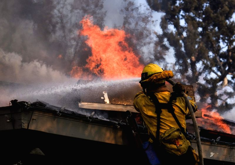LOS ANGELES, Dec. 7, 2017 - A firefighter tries to extinguish fire at a house in the Bel Air district of Los Angeles, the United States, Dec. 6, 2017. Los Angeles City Emergency Management Department ...