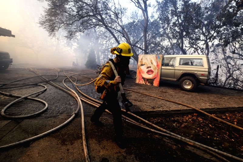 LOS ANGELES, Dec. 7, 2017 - A firefighter works at the Bel Air district of Los Angeles, the United States, Dec. 6, 2017. Los Angeles City Emergency Management Department on Wednesday night issued a ...