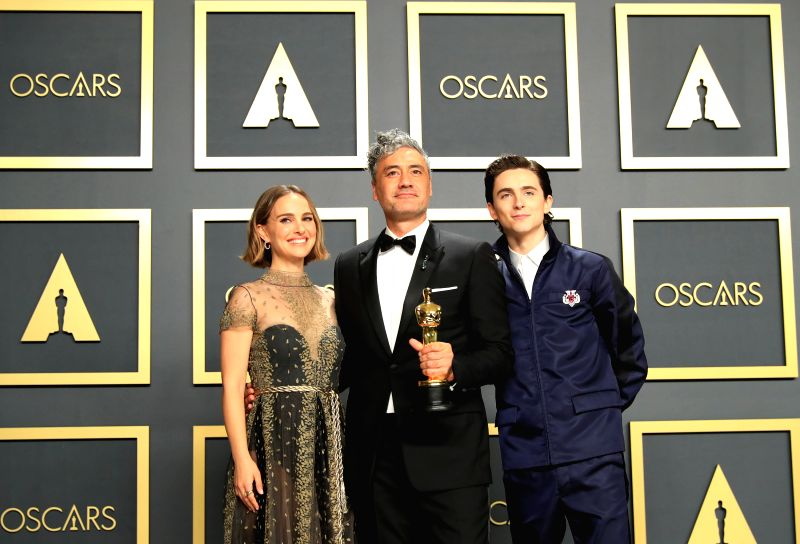"""LOS ANGELES, Feb. 10, 2020 (Xinhua) -- Presenters Natalie Portman (L) and Timothee Chalamet (R) poses for photos with Taika Waititi, winner of the award for best adapted screenplay for """"Jojo Rabbit"""", at the 92nd Academy Awards ceremony at the Dolby T"""