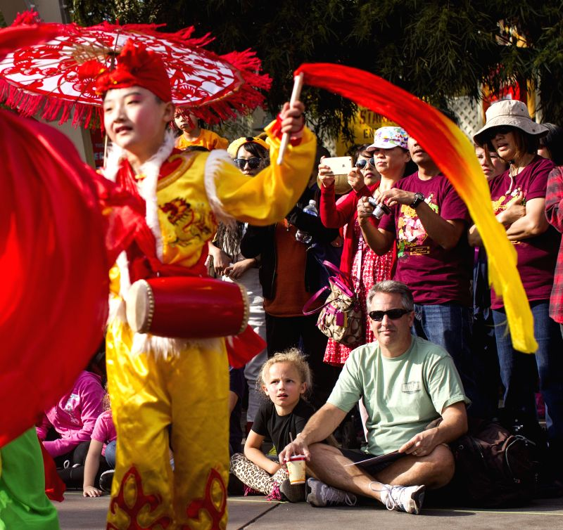 People watch members of Ansai waist drum and Luochuan yangko dance team from China performing at Disneyland, Los Angeles, California, the United States, on Feb. ...