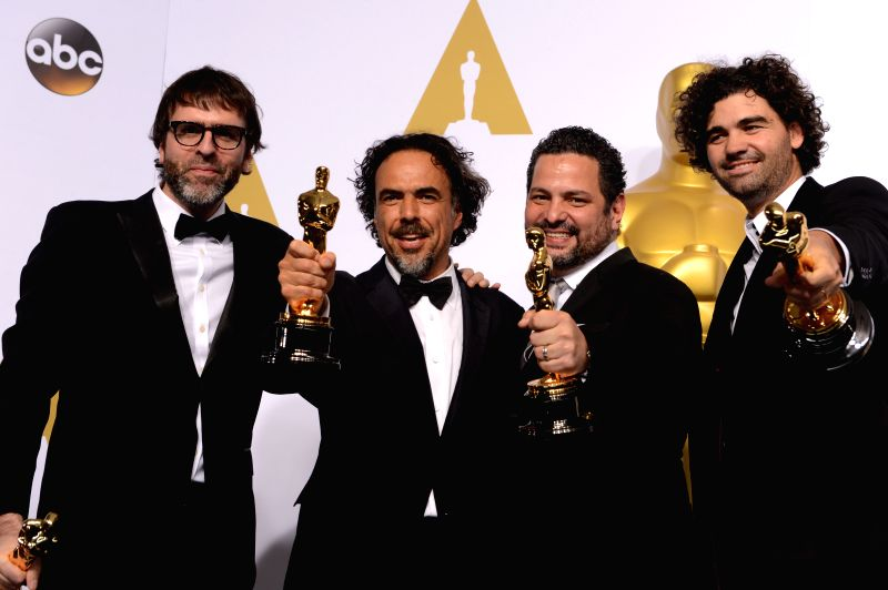 Alejandro G. Inarritu (2nd L), Nicolas Giacobone (1st L), Alexander Dinelaris (2nd R), and Armando Bo pose after winning the Best Original Screenplay award for ...