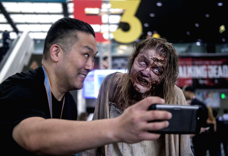 LOS ANGELES, June 13, 2018 - A visitor takes selfie photos with a zombie cosplayer at the Electronic Entertainment Expo 2018 (E3 2018) held in Los Angeles, the United States, on June 12, 2018.
