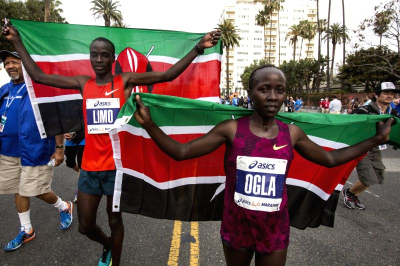 Daniel Limo (2nd R) and Olga Kimaiyo (1st R) of Kenya, celebrate with their national flags after they won the 30th Asics LA Marathon in Los Angeles, ...