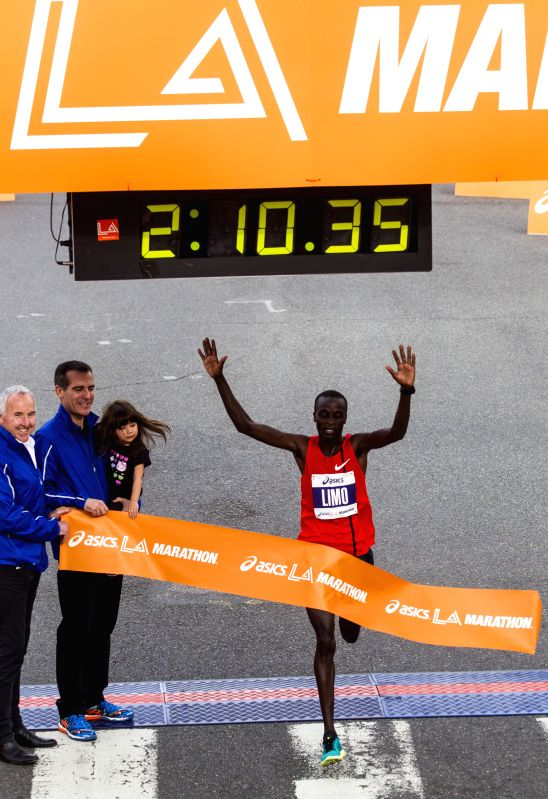 Daniel Limo (R) of Kenya crosses the finish line to win the the 30th Asics LA Marathon in Los Angeles, California, the United States, March 15, 2015. About ...