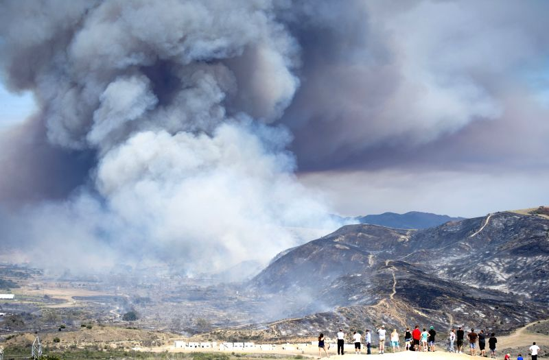 Local residents watch the wildfire on a mountain in San Diego, south California of the United States, May 16, 2014.