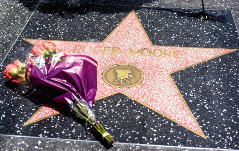 LOS ANGELES, May 24, 2017 - Flowers are placed on the Hollywood Walk of Fame star of Roger Moore in Los Angeles, the United States, on May 23, 2017. Moore, best known for his movie role as James ...