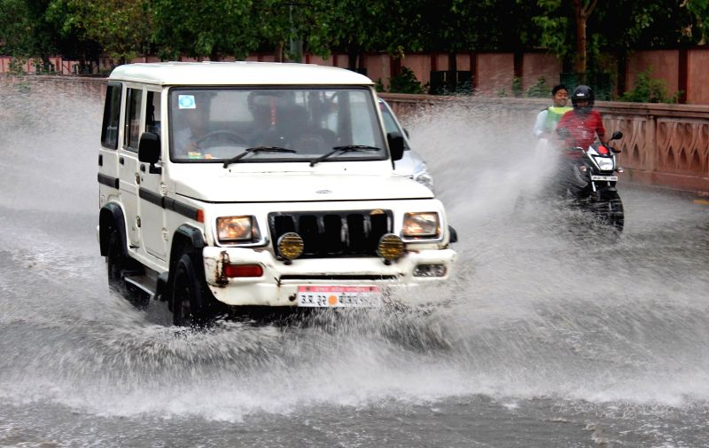 A car splashes water as it speeds through the water-logged roads of Lucknow on April 12, 2015.