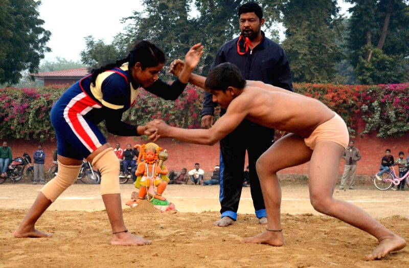 A female wrestler practice wrestling with a male wrestler during a mixed wrestling match at Harishchandra College in Lucknow on Dec. 6, 2014.