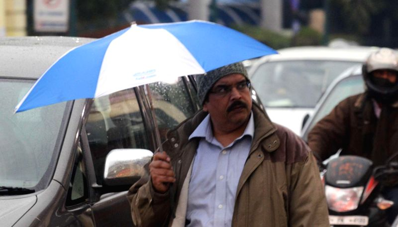 A man uses an umbrella to shield himself from winter rains in Lucknow on Jan 2, 2015.