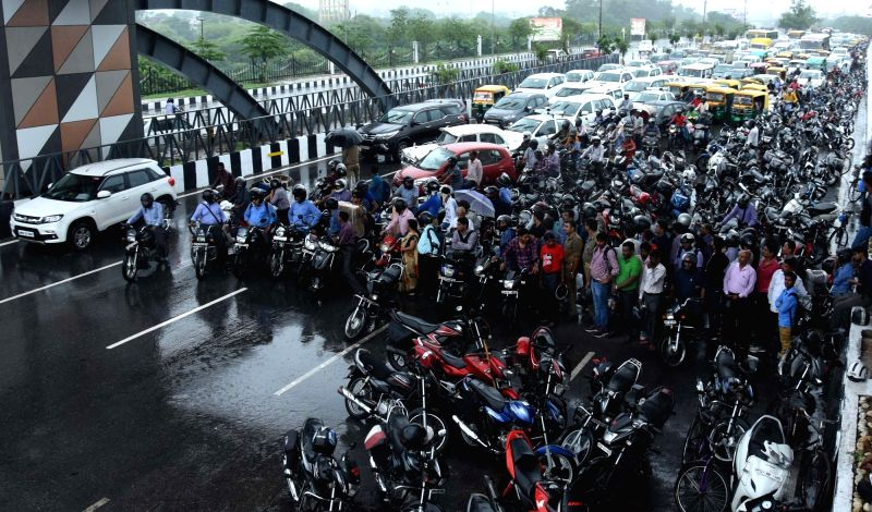 :Lucknow: A view of massive traffic jam as two-wheeler riders take shelter under a bridge, in Lucknow on July 26, 2018. (Photo: IANS).