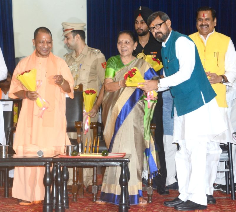 Lucknow: One of the 23 newly sworn-in Uttar Pradesh Cabinet Ministers being greeted by Governor Anandiben Patel and Chief Minister Yogi Adityanath at a swearing-in ceremony at the Raj Bhawan in Lucknow, on Aug 21, 2019. In what can be termed as a nea