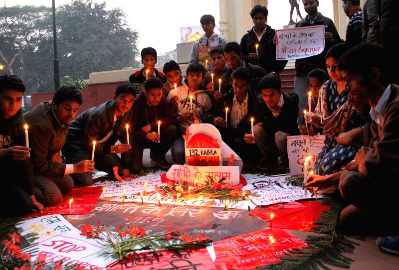 People participate in a candlelight vigil to condemn Tuesday's attack on the Army Public School in Peshawar, Pakistan, that claimed 148 lives mostly those of children, in Lucknow on Dec 18, .