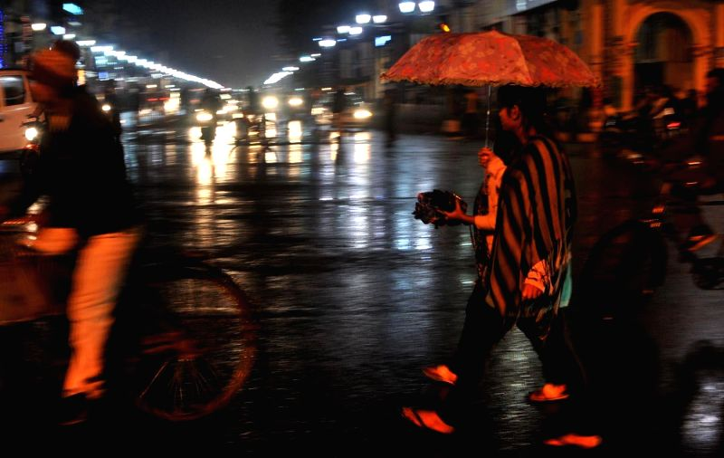 People running for shelter after heavy rain in Lucknow on Dec. 13, 2014. Brief spell of rain has dropped mercury by over seven degrees.