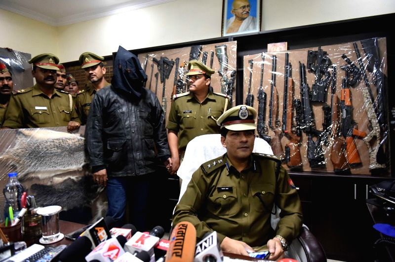 Police personnel present before press an arms smuggler, who was arrested with many sophisticated weapons in Lucknow, on Dec 17, 2014.