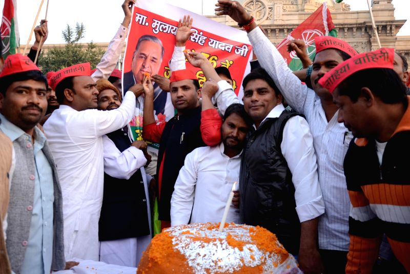 Samajwadi Party workers in a festive mood on the eve of party chief Mulayam Singh Yadav's birthday, with a 76 kg laddu in Lucknow, on Nov 21, 2014. - Mulayam Singh Yadav