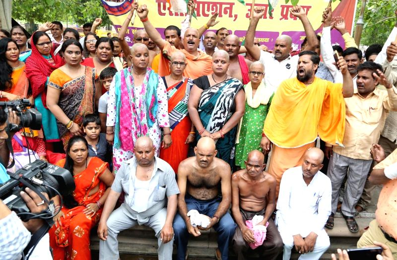 :Lucknow: 'Shiksha mitra' activists (contractual teachers) get their heads tonsured as they stage a demonstration to press for direct appointment of 30,000 candidates who have cleared ...