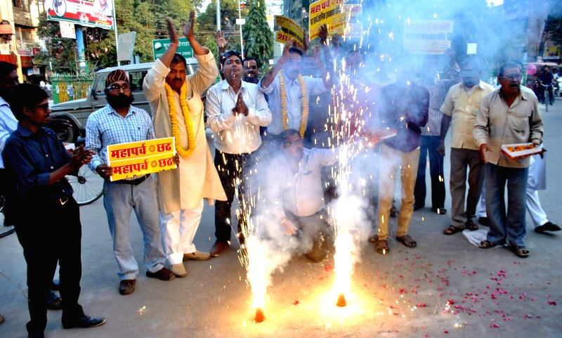 Lucknow : The members of Purwanchal Chhath Puja Samiti distribute sweets after Uttar Pradesh announced Chhath Puja as a public holiday in Lucknow on Nov 16, 2015.