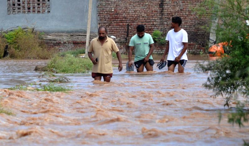 Ludhiana: : Locals struggle to cross an inundated road in Punjab's flood affected Ludhiana, on Aug 19, 2019.