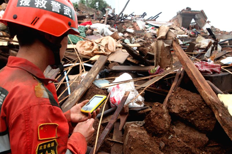 A rescuer searches for missing people at quake-hit Longquan Village of Longtoushan Town in Ludian County, southwest China's Yunnan Province, Aug. 4, 2014. At least ...