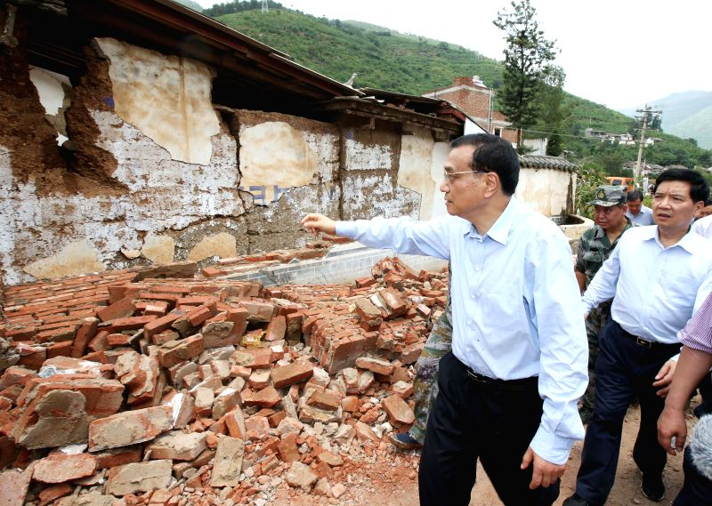 Chinese Premier Li Keqiang walks into Longtoushan Township of Ludian County to examine the situation of the earthquake and instruct the quake relief work in southwest