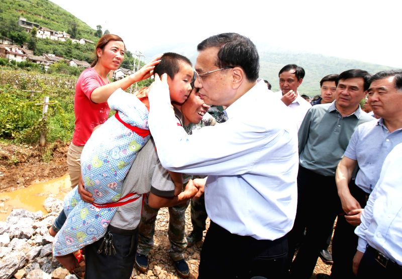 Chinese Premier Li Keqiang comforts a child at the earthquake zone in southwest China's Yunnan Province, Aug. 4, 2014. Premier Li Keqiang walked into Longtoushan ...