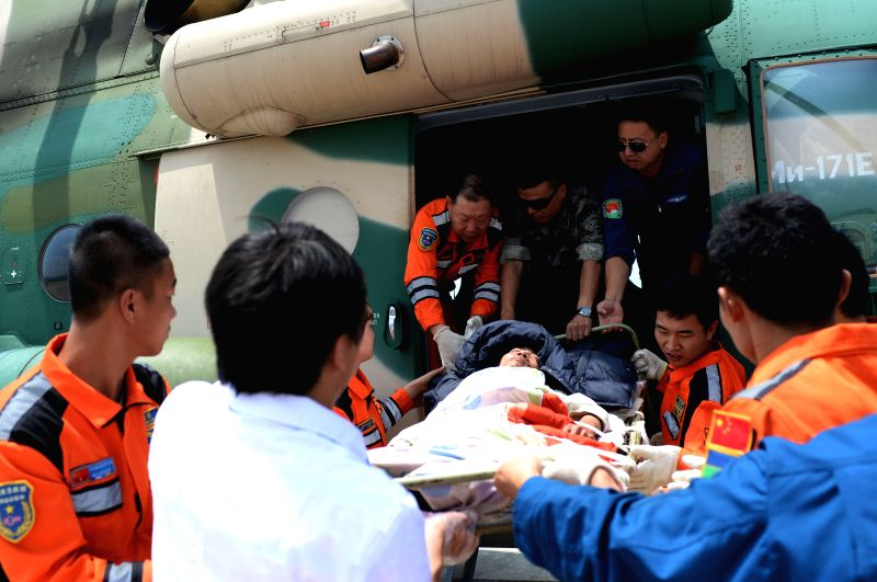 Rescuers transfer an injured person from a helicopter at an airport in Zhaotong City, southwest China's Yunnan Province, Aug. 6, 2014. Death toll from a 6.5-magnitude
