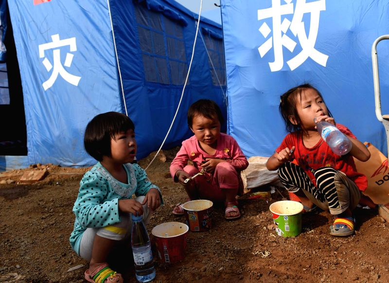 Lyu Mengjie (C), 5, and other two young girls have breakfast at a temporary resettlement in quake-hit Longtoushan Town of Ludian County, southwest China's Yunnan ...
