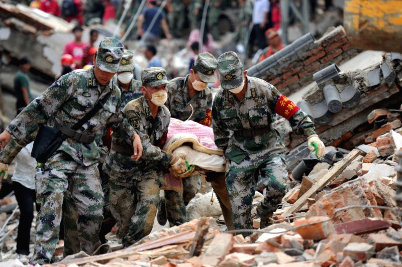 Rescuers carry the body of a victim in quake-hit Longtoushan Town of Ludian County, southwest China's Yunnan Province, Aug. 5, 2014.