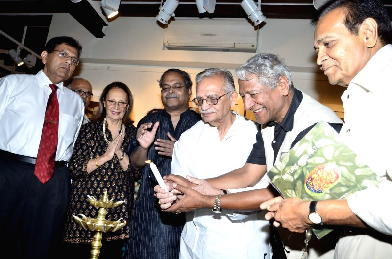 Lyricist Gulzar lights a candle during the inauguration of painting exhibition Epic on Rock Shelters by artist Ashok Bhowmick in Mumbai on April 15, 2014. - Ashok Bhowmick