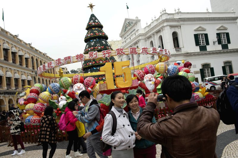 Tourists pose for a photo in front of a street decoration set up to celebrate the 15th anniversary of Macao's return to the motherland in the Macao Special ...