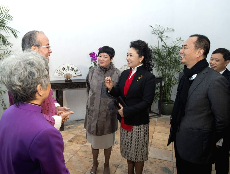 Chinese President Xi Jinping's wife Peng Liyuan (3rd R) talks with artists of the Cantonese Naamyam, a narrative folk singing popular in the Pearl River Delta region,