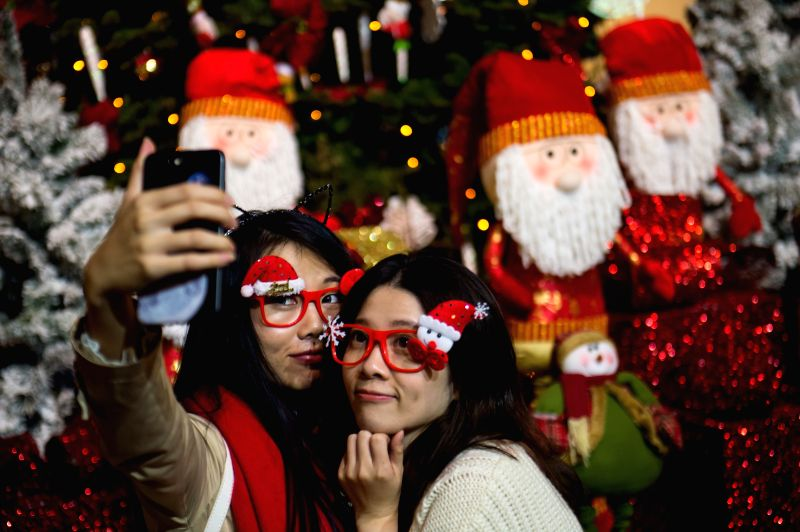 Tourists take a selfie in front of Christmas decorations at Largo do Senado, or Senado Square, in Macao, south China.