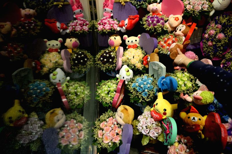 Photo taken on Feb. 13, 2015 shows clusters of flowers to be sold on the Valentine's Day at a flower shop in Macao, south China.
