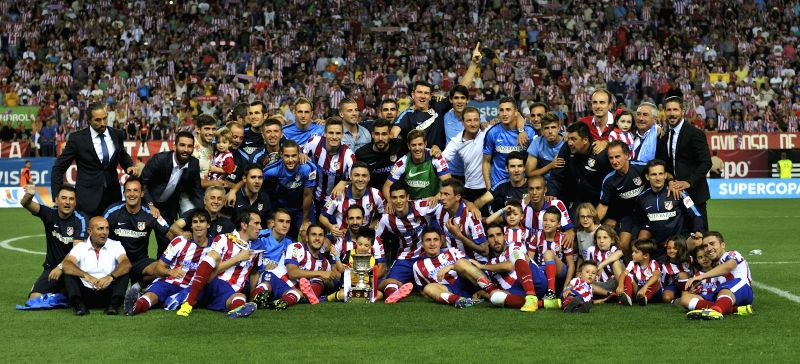 Atletico Madrid's players and staff celebrate with the Super Cup trophy after their Spanish Super Cup  match against Real Madrid at the Vicente Calderon Stadium in ..
