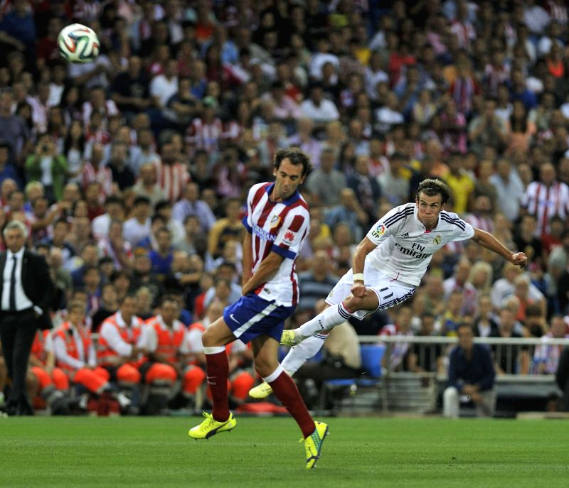 Real Madrid's Gareth Bale (R) shoots during their Spanish Super Cup match against Atletico Madrid at the Vicente Calderon Stadium in Madrid on August 22, 2014. ...