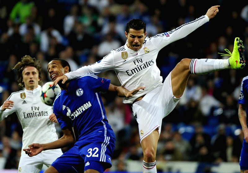 Real Madrid's Portuguese forward Cristiano Ronaldo (R) vies with Schalke 04's player Joel Matip (C) during the Champions League football match 2nd leg at Santiago ...