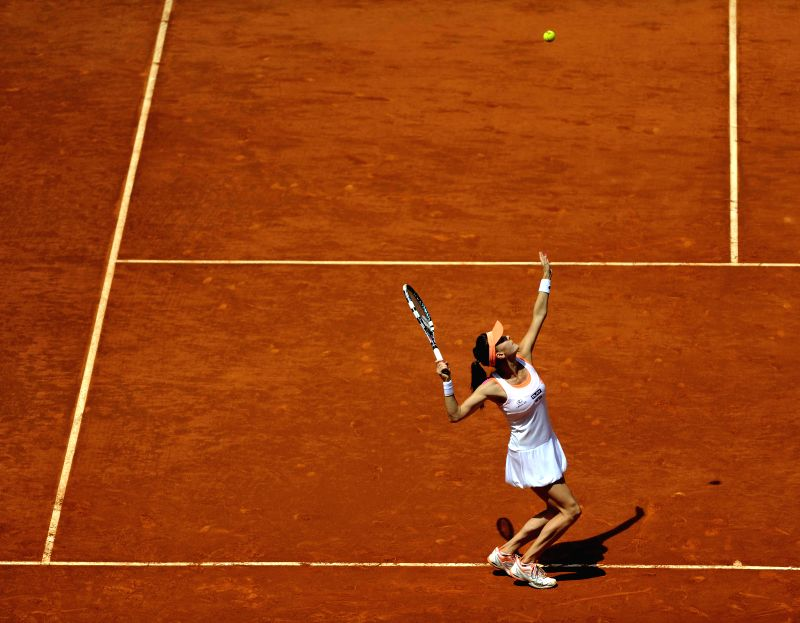 Agnieszka Radwanska of Poland serves to Maria Sharapova of Russia during the women's singles semifinal at the Madrid Open tennis tournament in Madrid, capital of ...