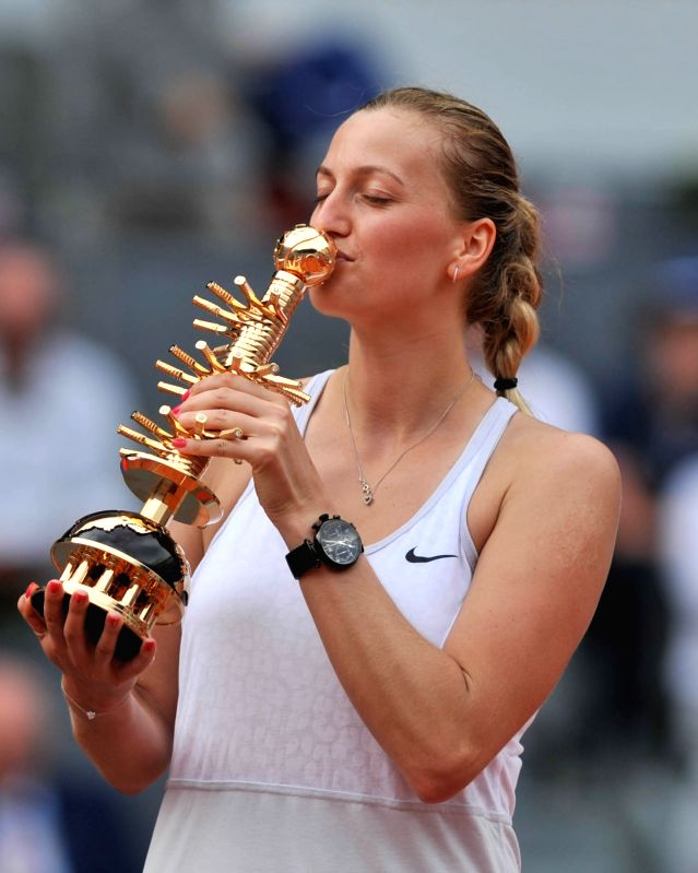 Petra Kvitova of the Czech Republic kisses the trophy during the awarding ceremony after the final match against Svetlana Kuznetsova of Russia at the WTA Madrid Open ...