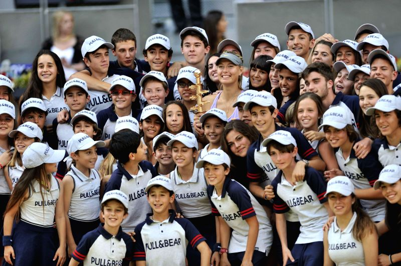 Maria Sharapova (C) of Russia poses with the ball kids during the awarding ceremony after the women's singles final match against Simona Halep of Romania at the 2014 .