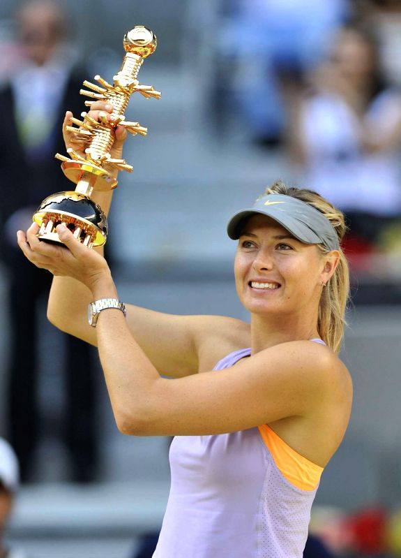 Maria Sharapova of Russia holds up the trophy during the awarding ceremony after the women's singles final match against Simona Halep of Romania at the 2014 Madrid ...