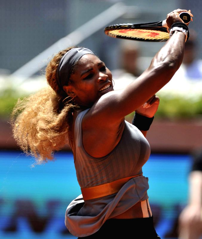 Photo: Serena Williams of the United States returns a shot to Spain's Carla Suarez Navarro during the women's singles third round at the Madrid Open tennis tournament .