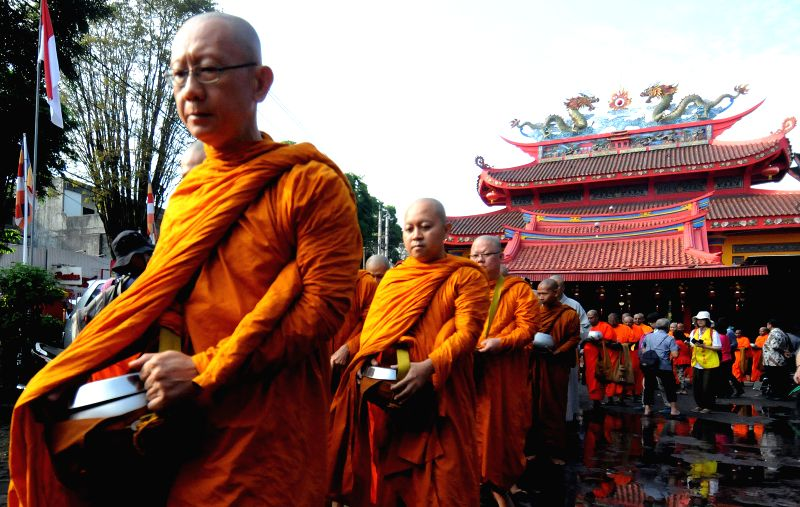 Buddhist monks collect alms from Buddhist followers ahead of Vesak Day at a shopping area in Magelang, Central Java, Indonesia, on May 14, 2014. Indonesian ...