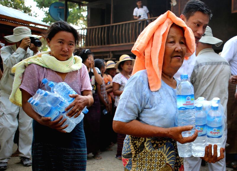 MAGWAY, May 9, 2016 - Residents facing water shortage during the dry season receive bottles of drinking water from donors of Chinese companies and the Chinese Embassy, at a village of Saku Township ...
