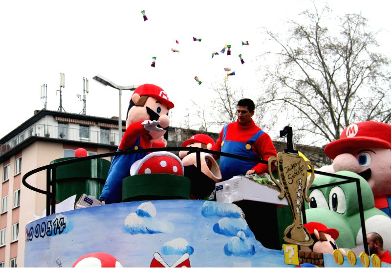 MAINZ(GERMANY), Feb. 17, 2015 An actor in the costume of Super Mario throws candies during the traditional Rose Monday carnival parade in the western German city of Mainz, Feb. 16, 2015.