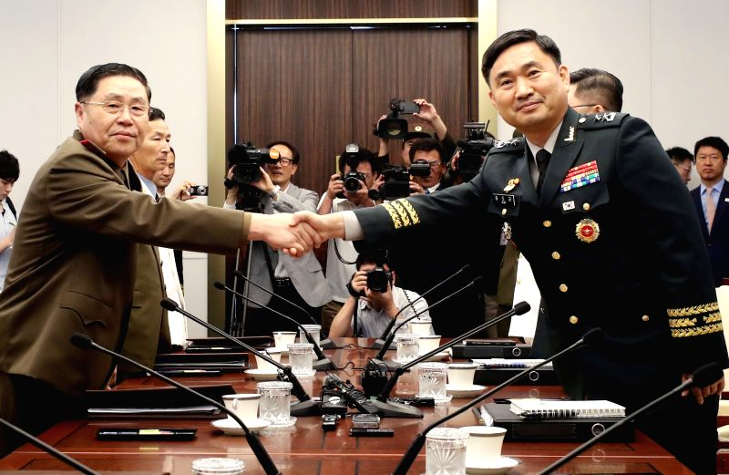 Major Gen. Kim Do-gyun (R), South Korea's chief delegate, and his North Korean counterpart Lt, Gen. An Ik-san shake hands at the start of inter-Korean military talks at the truce village ...