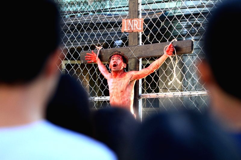 Devotee Jhofer Carpio participates in a re-enactment of the crucifixion of Jesus Christ on Good Friday in Makati City, the Philippines, April 18, 2014. Dozens .