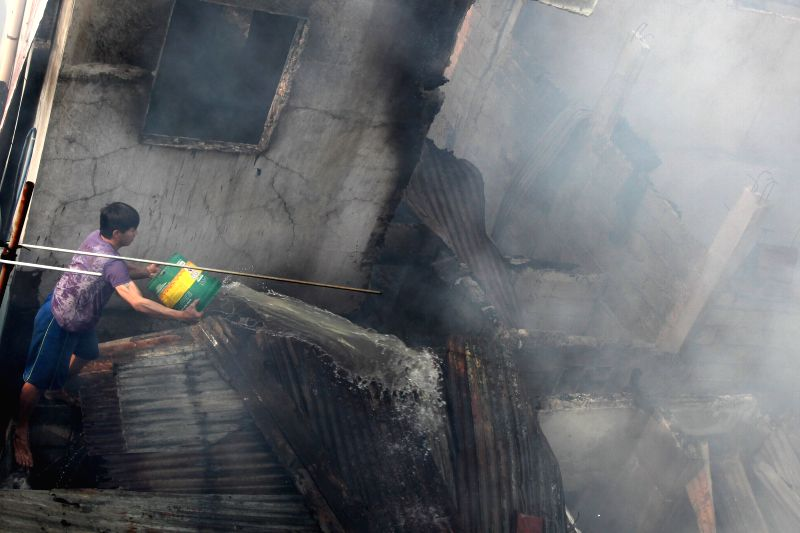 A resident tries to put out a fire at a residential area in Malabon City, the Philippines, Feb. 17, 2015. About 50 homes were razed in the fire happened in ...