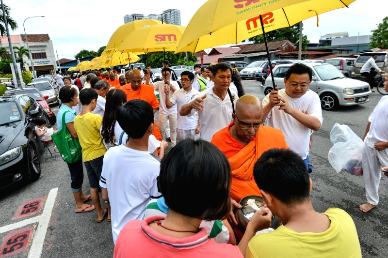 MALACCA, May 21, 2016 - Buddhists give food to monks during the Vesak in Malacca, Malaysia, May 21, 2016. Vesak, also known as the Buddha Day, is a holy day observed by Buddhists in many Asian ...