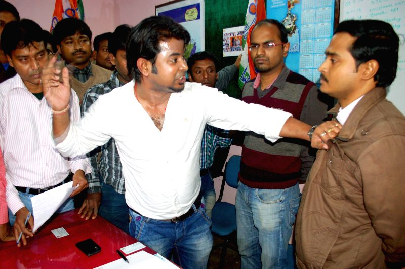 A Trinamool Congress leader manhandles a WBSEB engineer at the later's office in Malda of West Bengal on Dec 5, 2014.